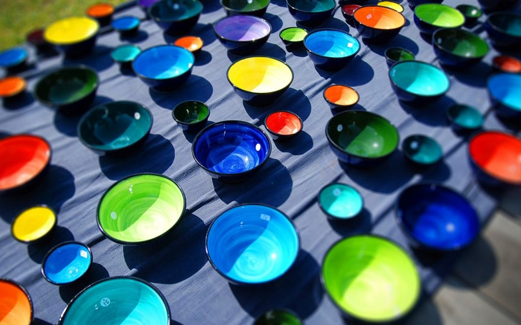 Bowls of various colors and sizes arranged neatly across a table. This photograph demonstrates an abstract pattern rather than focusing on a single object.