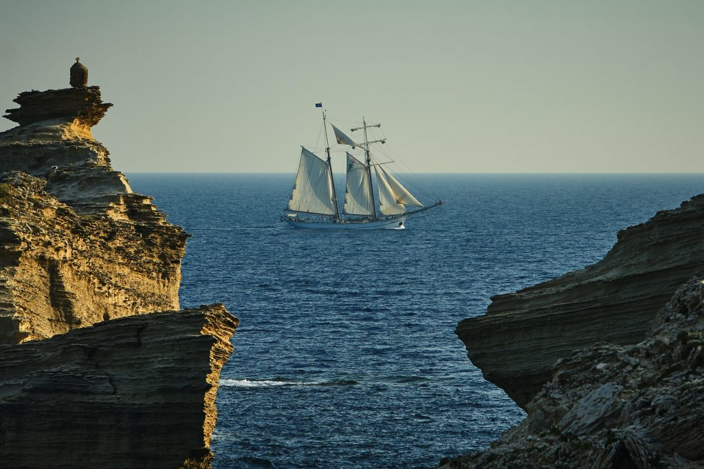 Photo of a three-masted sailboat out in the ocean. The sailboat helps to add drama to the photo that would otherwise be just a photo of the ocean showing between rock faces.