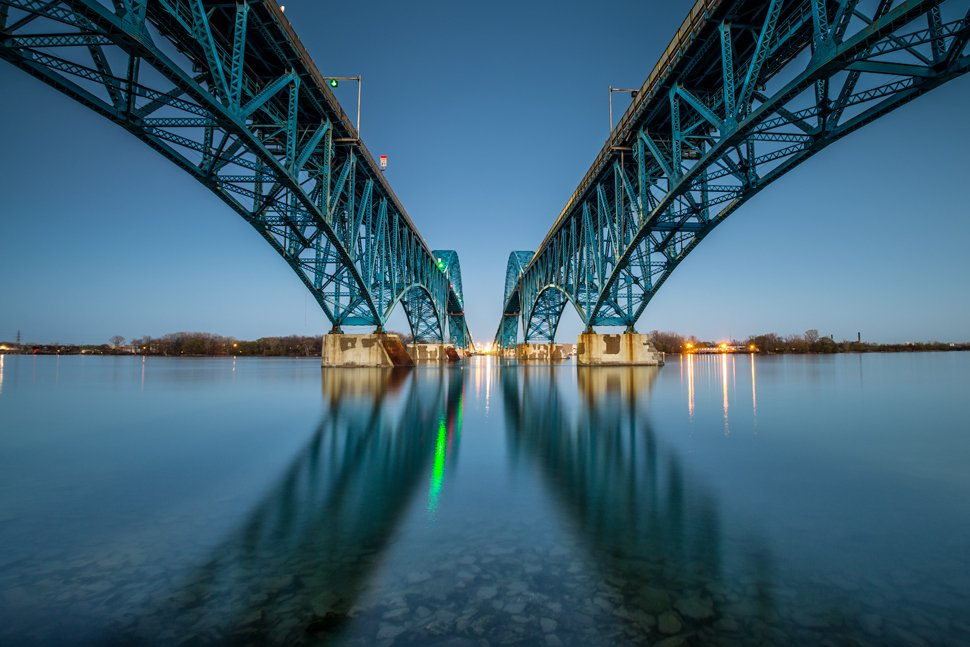 Photo from underneath a pair of bridges that extend symmetrically across a river.